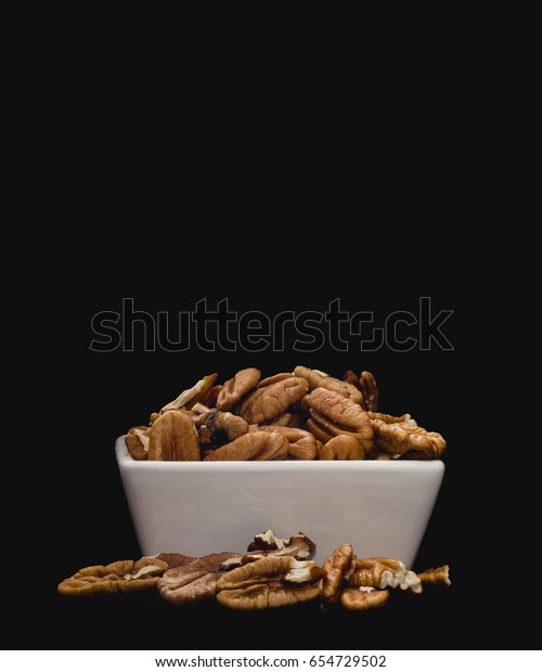 White ceramic bowl containing pecan nuts on solid black background