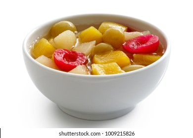 White ceramic bowl of fruit cocktail isolated on white.