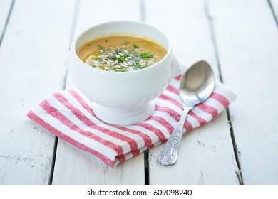 white ceramic bowl of vegetarian vegan soup dressed garnish seeds cloth spoon