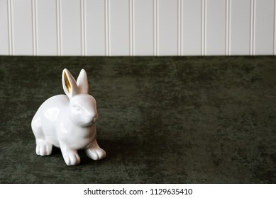 White ceramic bunny with gold ears on a dark green fabric background with a white bead board wall