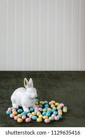 White ceramic bunny with gold ears on a dark green fabric background with a white bead board wall, and pastel Easter candy eggs in yellow, pink, green, and blue