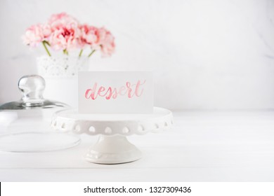 """White ceramic cake plate and card with word """"dessert"""" on it. Pink flowers on background."""