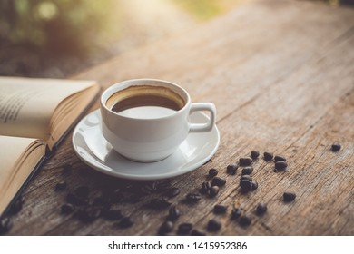 White ceramic coffee cup of black hot americano on wooden table or counter with book