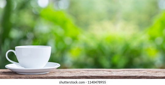 White ceramic coffee cup on wooden table or counter with green nature light blur background and space for text, design, photo montage or advertising
