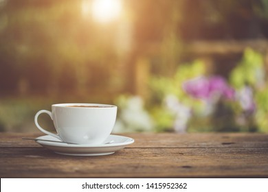 White ceramic coffee cup on wooden table or counter with morning nature light in garden concept