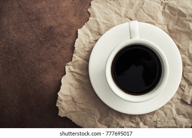 white ceramic cup with black coffee on craft paper, stone table, top view