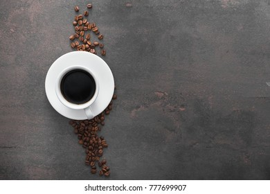white ceramic cup with black coffee and ground grains on stone table