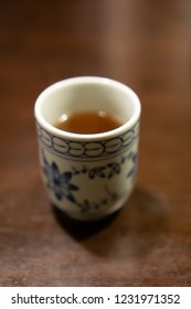 White ceramic cup of Japanese roasted green tea on a table in traditional Japanese restaurant (The tea is called Hojicha and it looks like Chinese oolong tea)