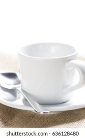 White ceramic cup on a linen tablecloth