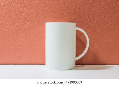White ceramic cup with orange wall and white floor, Thailand.