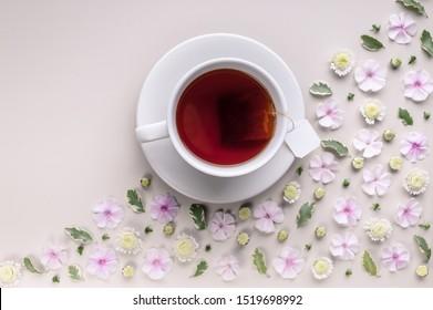 Weiße keramische Tasse mit Tee auf einem floralen Eckmuster auf beigem Hintergrund. Blumentee-Konzept. Teebeutel. Draufsicht