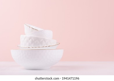 White ceramic dishes with thin gold border, different tracery form on white wood table in delicate soft light pastel pink interior.