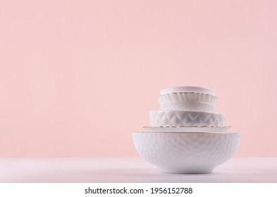 White ceramic dishes with thin gold border, different tracery form on white wood table in delicate pastel pink interior.