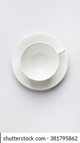 White ceramic empty cup on saucer top view