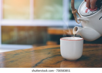 White ceramic kettle pouring hot tea into a cup on wooden table with morning sunlight and copy space in vintage style, close up