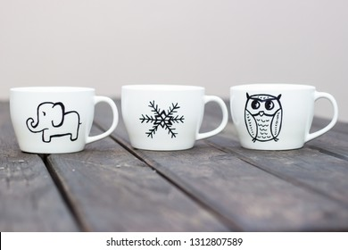 White ceramic mugs with permanent marker drawing on wooden table diy cup gift handmade sharpie mugs personalised party favors