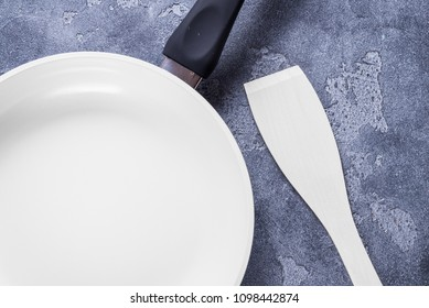 White ceramic pan and wood scapula on grey background