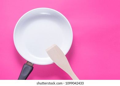 White ceramic pan and wood scapula on pink background