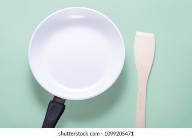 White ceramic pan and wood scapula on blue background