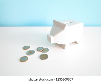 White ceramic piggy bank with euro coins on the table