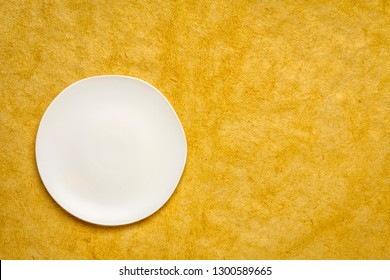 white ceramic plate with an irregular edge on a sunflower yellow handmade Huun Mayan  paper  with a copy space