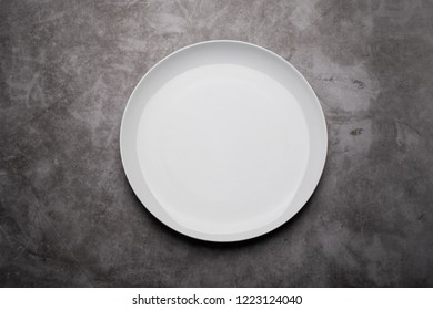 White ceramic plate on concrete texture background