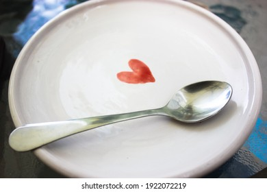 A white ceramic saucer with a picture of a red heart and a silver teaspoon on the surface of the plate. Clean utensils. High quality photo.