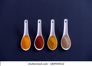 WHITE CERAMIC SPOONS ALIGNED WITH DIFFERENT KINDS OF SPICES ON BLACK BACKGROUND. MINIMALIST GASTRONOMY CONCEPT. TOP VIEW.
