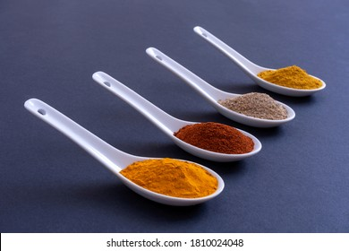 WHITE CERAMIC SPOONS ALIGNED WITH DIFFERENT KINDS OF SPICES ON BLACK BACKGROUND. MINIMALIST GASTRONOMY CONCEPT.