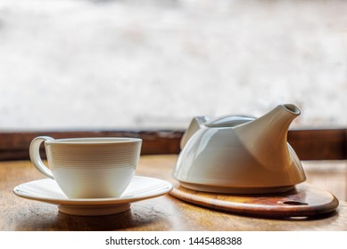 White ceramic tea pot and cup on a wooden table