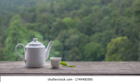 White ceramic teapot and teacup with fresh green tea leaves on wooden table in blurred natural background