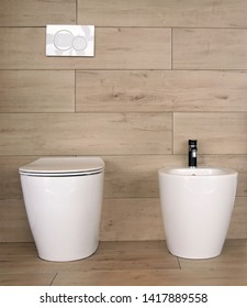 White ceramic toilet and bidet in   a bathroom made of stoneware with wood effect
