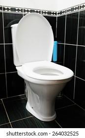 White ceramic toilet in black tiled bathroom
