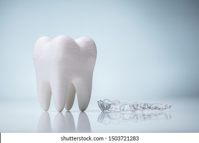 White Ceramic Tooth Model And Transparent Mouth Guard Over Reflective Desk