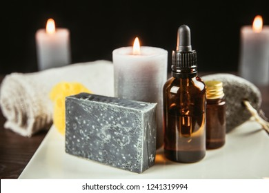 White ceramic tray with group of different spa essentials, beard oil, gray soap, natural sea sponge, candle, aroma oil on wooden and black background. Father, brother or husband gift idea concept.