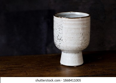 A white ceramic vase on a wooden table top with a dark cloth background