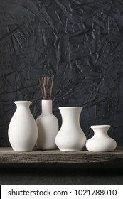 White ceramic vases on distressed wooden shelf against rough plaster black wall. Home decor.