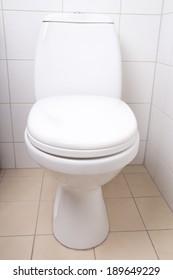 white ceramics WC pan in tiled bathroom