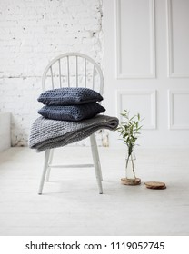 white chair in bright livingroom. gray knitted pillows on the chair. plant in a glass. luxury scandinavian interior