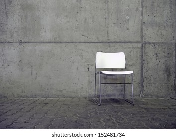 white chair in front of face concrete wall