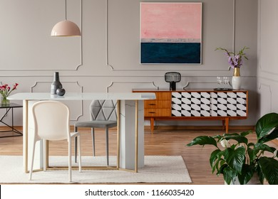 White chair and marble table under pink lamp in eclectic living room interior with painting above cabinet. Real photo