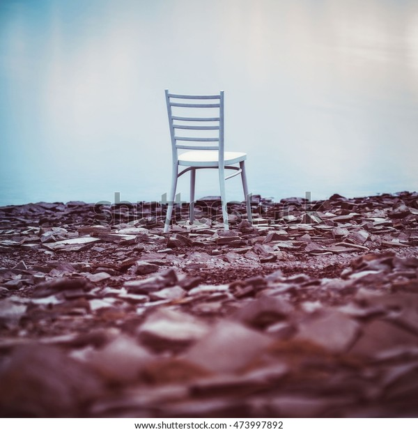 White chair on the coast dam. Stylized photo of white chairs near the dam.