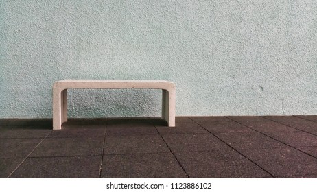 white chair on white concrete wall with brown floor