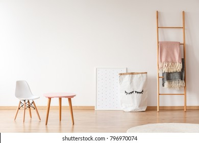 White chair and pink wooden table standing in baby room with material basket, blankets hanging on ladder and poster with dots