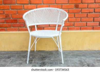 white chair with red brick background.