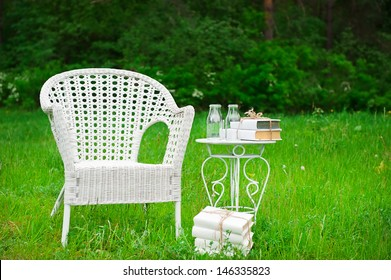 White chair, a table and books on the green lawn