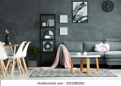White chairs at dining table in dark living room interior with black clock and poster on concrete wall