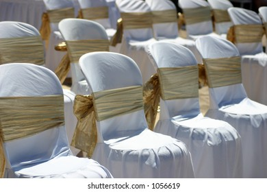 White chairs with gold ribbon at a beach wedding