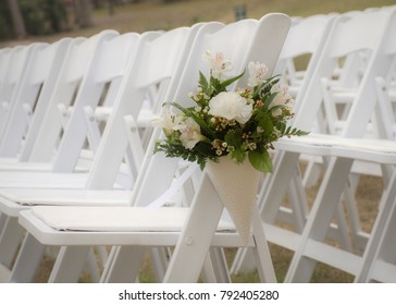 white chairs lined up for an event accompanied by a bouquet of white flowers.