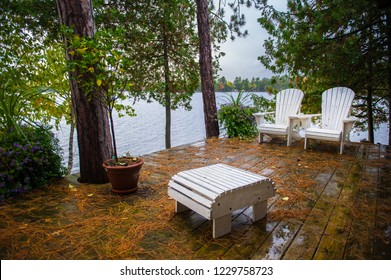 White chairs on a cottage porch facing a calm lake during fall season.